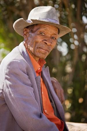 壊れたと高齢者のアフリカ人の肖像画を持っていたし、古いスーツ