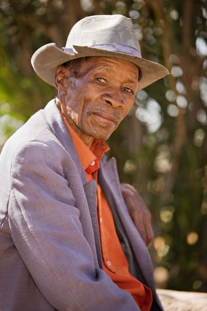 scarcity: Portrait of elderly  african man with a broken had and old suit