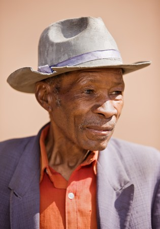Portrait of elderly  african man with a broken had and old suit  photo