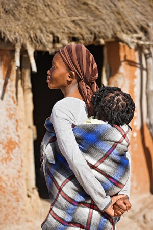 braids: African mother carry child in a traditional way in front of the hut