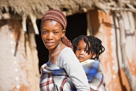 アフリカの母、小屋の前に伝統的な方法で子供を運ぶ