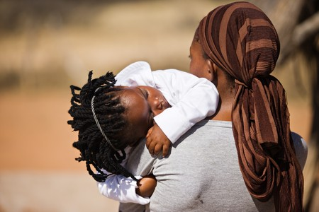 world village: african family, mother and child, living  in a very poor village near Kalahari desert