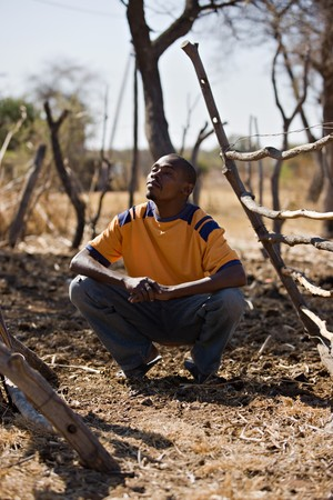 african man sitting in the cattle kraal, in the village Stock Photo