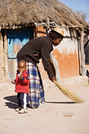 Young mother cleaning the yard with a broom, in front of traditional african house