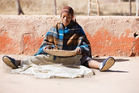 Portrait of African woman with a basket of sorghum, staple food in africa 写真素材