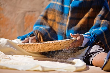 Portrait of African woman with a basket sieve straining sorghum, staple food in Africa