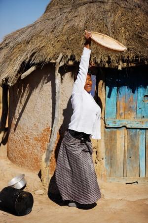 sorgo: Retrato de mujer africana frente a la choza con una cesta de sorgo,