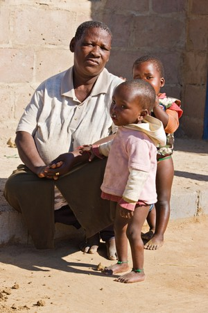 world village: african family, grandmother and the grandchildren, living  in a very poor village near Kalahari desert