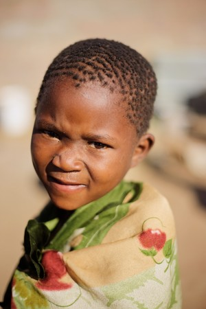 needy: african boy living in a very poor community in a village near Kalahari desert