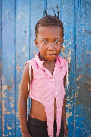african girl in front of a blue door in a village near Kalahari desert