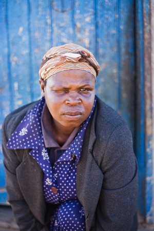 sightless: Homeless half blind African woman sitting in front of a shacks door