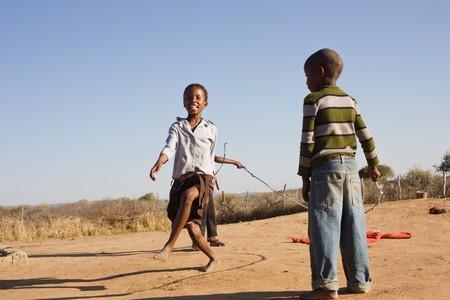 african children jumping rope in the sand, Mmankodi village Botswana 写真素材