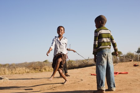 poor african: african children jumping rope in the sand, Mmankodi village Botswana Stock Photo