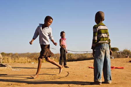 world village: african children jumping rope in the sand, Mmankodi village Botswana Stock Photo