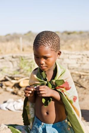 カラハリ砂漠の近くの村で非常に貧しいコミュニティに住んでいるアフリカの少年