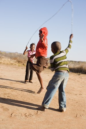 african children jumping rope in the sand, Mmankodi village Botswana Stock Photo