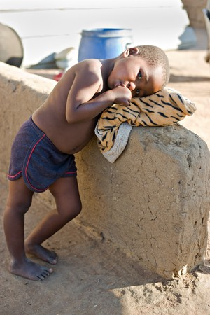 needy: african girl resting in the backyard in a village near Kalahari desert Stock Photo