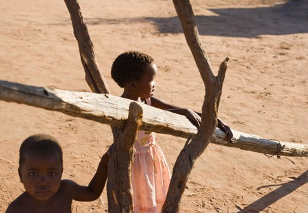 brother and sister hanging out in the yard in an village near Kalahari desert Stock Photo
