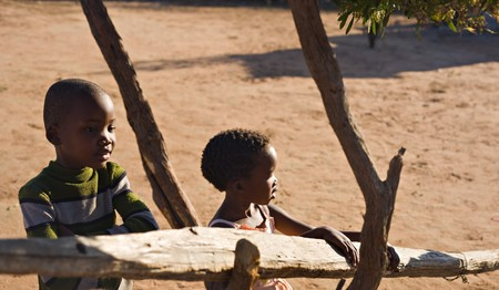 brother and sister hanging out in the yard in an village near kalahari desert
