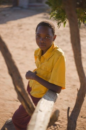 african boy with yellow shirt sitting in the shade in a village near Kalahari desert