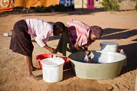 scarcity: african young girl and an elderly woman washing clothes in the yard