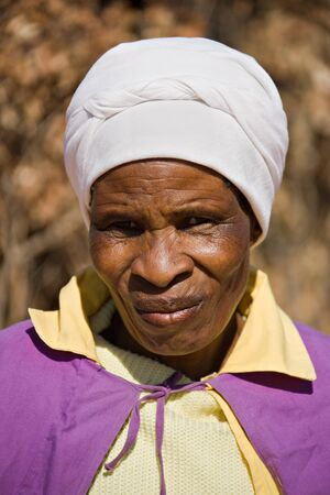 poor woman: Old african woman in the village dressed in church uniform  Stock Photo