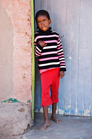 Village African child standing in front of the door photo