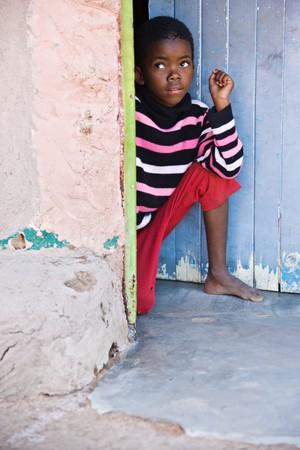 Village African child kneeling  in front of the door