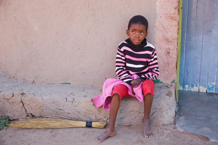 Village African child sitting in front of the door