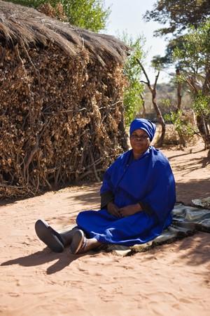 Infront vecchia donna africana della capanna, vestito in uniforme chiesa Archivio Fotografico