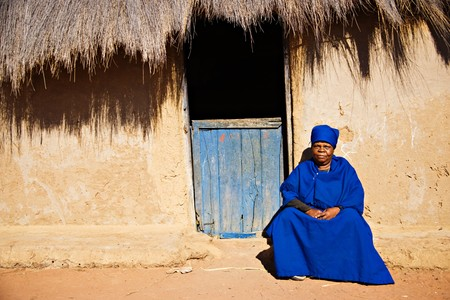 Old african woman in the village dressed in church uniform  Stock Photo