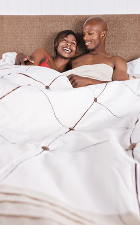 african american couple in bed having fun photo