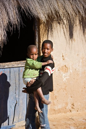 world village: brother and sister in front of a hut  in an african village Stock Photo