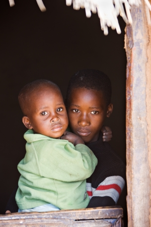 poor woman: Small African children in the door of the village house