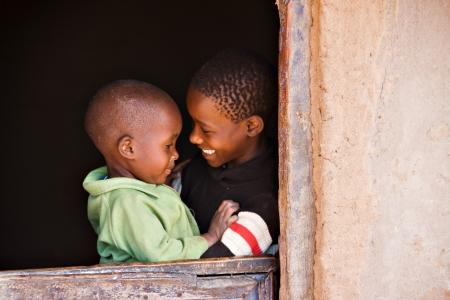 兄と妹のアフリカの村の小屋のドア 写真素材