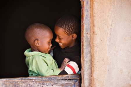 brother and sister in the door of a hut  in an african village