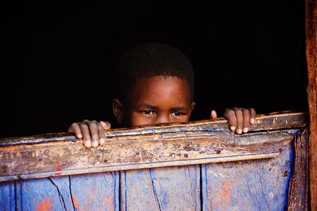 村の家のドアの後ろに小さいアフリカの子供、ロモを見る 写真素材
