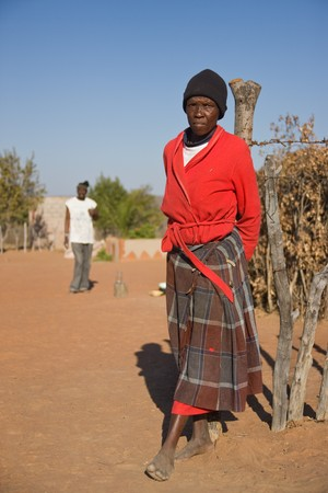 Old african woman in the village resting against the wooden fence  photo