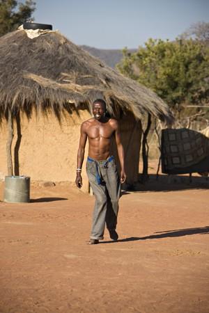 crippled: Crippled African man walking barefoot in the hot sand of Kalahari