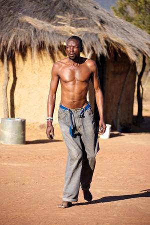 Crippled African man walking barefoot in the hot sand of Kalahari photo