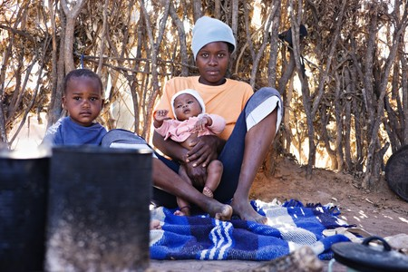 Portrait of African children and mother in the hut, location Mankodi village, Botswana Stock Photo