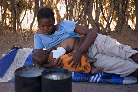 African mother feeding the baby , location Mankodi village , Botswana photo