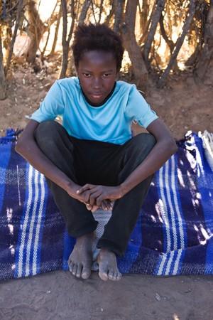 Portrait of African child in the hut, on the blanket, location Mmankodi village, Botswana Stock Photo