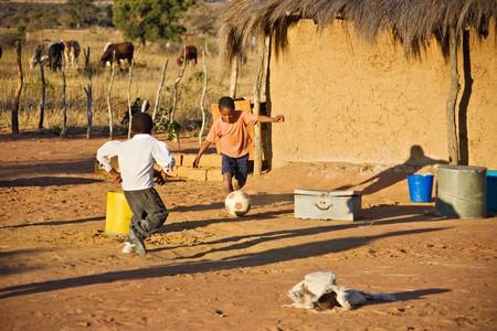 ni�os africanos: Los ni�os africanos jugando al f�tbol en la aldea despu�s de ganado Foto de archivo
