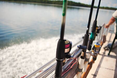 fisherman in a boat on Zambezi river, Africa, fishing rods with the reel photo