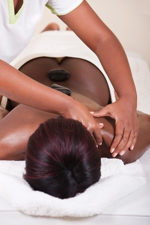 lifestyle, African American woman having a stone massage treat at the spa photo