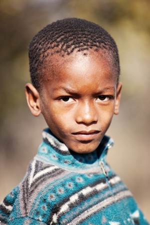 skinny african child with a jacket warming in the sun