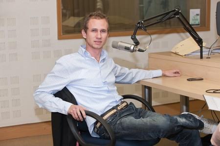 joven varón de raza blanca en frente del micrófono en la estación de radio, concepto general, entrevista, orador, DJ.