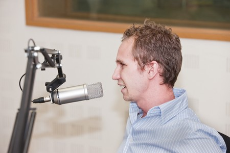amplified: young Caucasian male in front of the microphone at the radio station, general concept, interview, speaker, DJ.