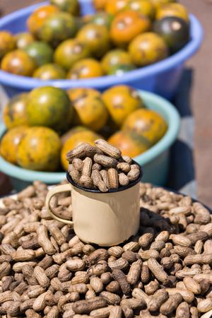 african street vendors selling peanuts, monkey oranges,